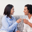 Couple having sparkling wine on the couch — Stock Photo