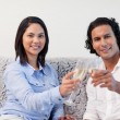 Couple celebrating with sparkling wine on the sofa — Stock Photo