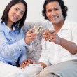 Couple celebrating with sparkling wine in the living room — Stock Photo