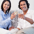 Happy couple drinking sparkling wine on the sofa — Stock Photo #11209963