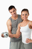 Portrait of a smiling man helping a woman to work out — Stock Photo
