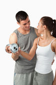 Portrait of a man helping a young woman to work out — Stock Photo