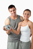 Portrait of a man helping a smiling woman to work out — Stock Photo