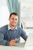 Hombre sonriente con tarjeta de crédito en su cuaderno — Foto de Stock