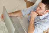 Sleepy businessman sitting at his notebook — Stock Photo