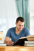 Smiling student reviewing his subject material — Stock Photo