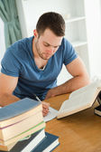 Student working hard on his book report — Stock Photo