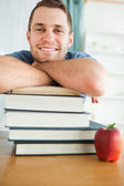 Smiling student with a stack of books — Stock Photo