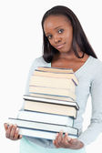 Sad smiling woman with pile of books — Stock Photo