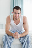 Portrait of a smiling man sitting on his bed — Stock Photo