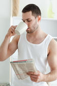 Portrait of a young man drinking tea while reading the news — Stock Photo