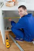 Portrait of a smiling repair man measuring something — Stock Photo