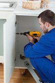 Portrait of a handyman fixing a door — Stock Photo