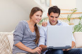Smiling couple using a laptop — Stockfoto