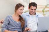 Delighted couple using a laptop — Stock Photo