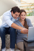 Portrait of a startled couple using a laptop — Stock Photo