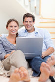 Portrait of a couple using a notebook while lying on a sofa — Stock Photo