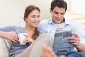 Para czytanie newsów leżąc na kanapie — Zdjęcie stockowe
