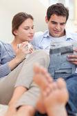 Para czytanie gazety leżąc na kanapie — Zdjęcie stockowe