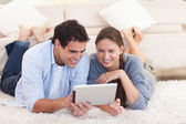 Smiling couple using a tablet computer — Stock Photo