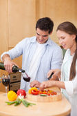 Portrait of a cute man pouring a glass of wine while his wife is — Stock Photo