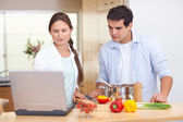 Couple using a laptop to cook — Stock Photo