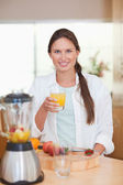Portrait of a young woman drinking fresh fruits juice — Stock Photo