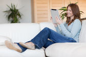 Smiling woman with tablet on the sofa — Stok fotoğraf