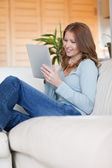 Smiling woman on the sofa with her tablet — Stock Photo