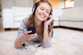 Young woman lying on the carpet listening to music — Stock Photo