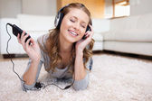Woman lying on the carpet enjoying music — Stock Photo