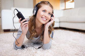 Woman lying in the living room enjoying music — Stock Photo