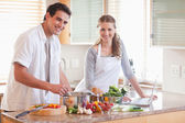 Couple using notebook to look up recipe — Stock Photo