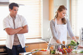 Man watches his girlfriend cooking — Stock Photo