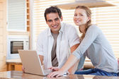 Couple with notebook in the kitchen — Stock Photo