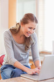 Woman surfing the internet in the kitchen — Stock Photo