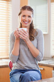 Smiling woman having a cup of coffee in the kitchen — Stock Photo