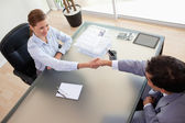 顾问的视图上方与她的客户握手 — 图库照片