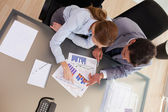 Above view of consultant analyzing statistics with her client — Stock Photo