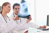 Doctor showing her colleague an x-ray — Stock Photo