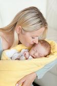 Affectionate mother kissing her sleeping baby in her arms — Stock Photo