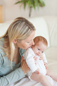 Mother on the sofa holding her baby — Stock Photo