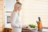 Side view of woman slicing ingredients for her salad — Stock Photo