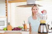 Woman dropping strawberry into the blender — Stock Photo