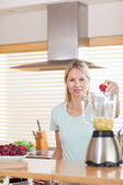 Woman putting strawberry into the blender — Foto de Stock