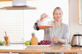 Woman pouring self made juice into a glass — Stock Photo