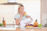 Woman taking a sip of juice while holding her baby — Stock Photo