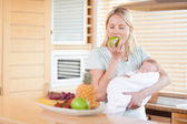 Woman eating an apple while holding her baby — Stock Photo