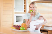 Woman with baby on her arms eating an apple — Stock Photo