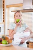 宝宝有一个苹果她胳膊上的女人 — 图库照片